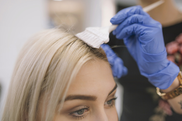 close-up-of-hairdresser-applying-dye-with-brush_23-2147769759